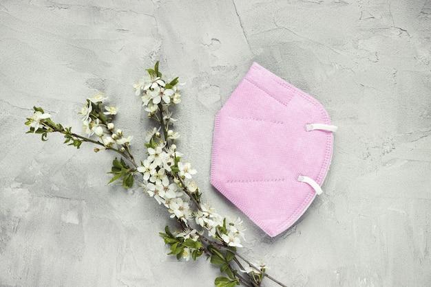 Roze gezichtsmasker met bloemtakken op betonnen ondergrond