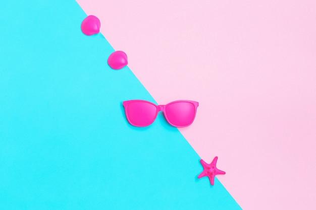 Roze glazen en zeeschelpen op kleurrijk.