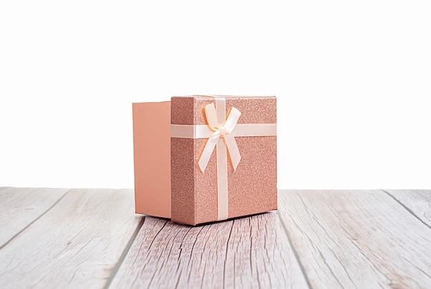 Roze gouden papieren geschenkdoos met dun beige lint op houten tafel, kopieer ruimte voor uw tekst