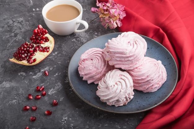 Roze granaatappel zelfgemaakte zephyr of marshmallow met kopje koffie op een zwarte betonnen ondergrond met rode textiel