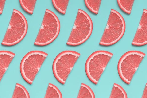Roze grapefruit isoetric patroon op pastel blauwe achtergrond
