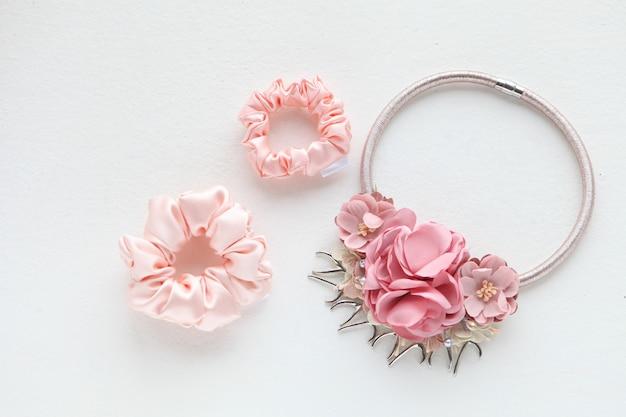 Roze haaraccessoires met rozen zijde roze scrunchy op witte achtergrond plat lag