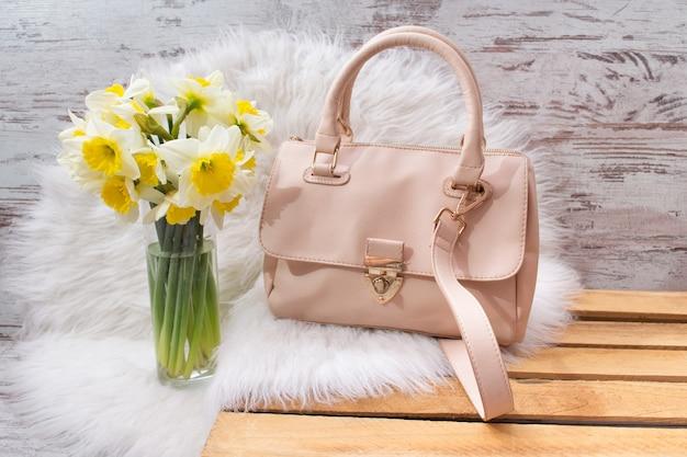 Roze hahdbag en boeket van narcissen op wit bont. modieus concept