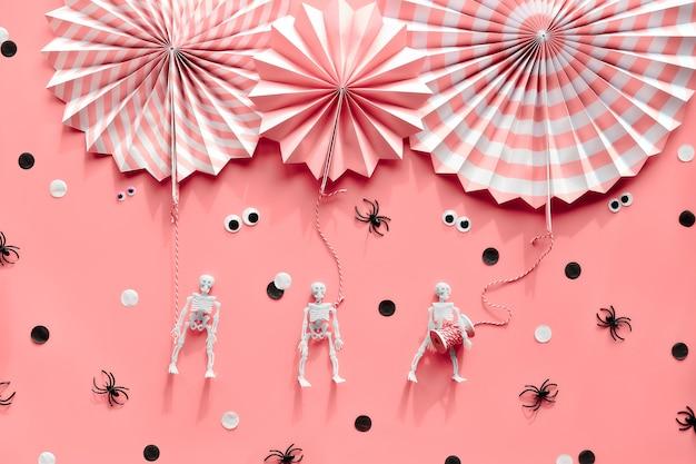 Roze halloween, plat leggen. gestreepte papieren waaiers, spinnen, skeletten, wiebelogen. zwart witte confetti.