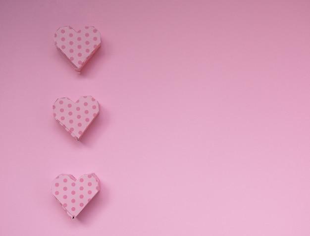 Roze handgemaakte hartvormige geschenkdozen op een pastel roze achtergrond minimaal concept