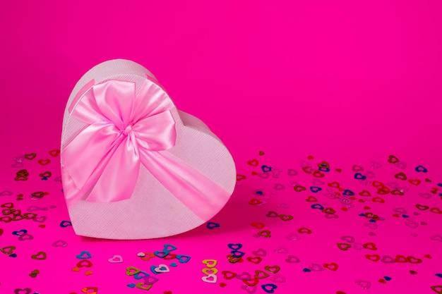 Roze hart doos met strik op roze achtergrond valentijnsdag geschenk