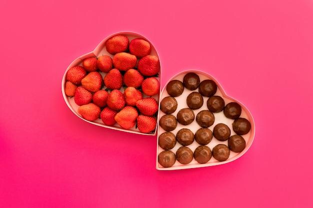 Roze hart geschenkdoos voor valentijnsdag op een roze achtergrond met aardbeien en chocolade.
