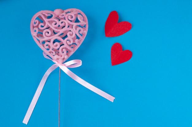 Roze hart met kleine rode harten op blauwe achtergrond