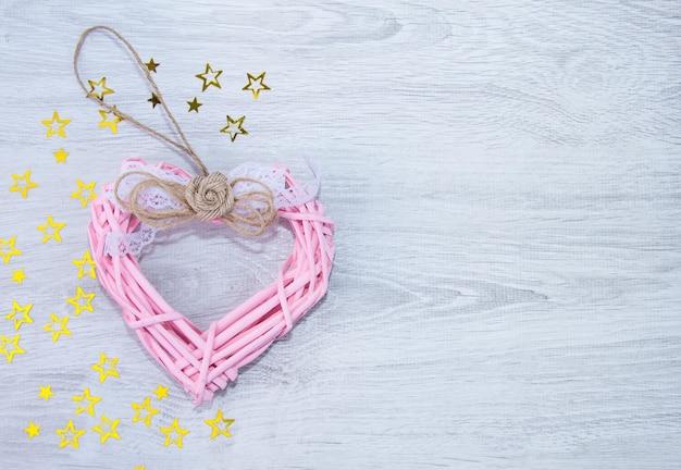 Roze hart op een houten achtergrond. gele sterren op een lichte achtergrond. het uitzicht vanaf de top. ruimte voor tekst.