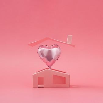 Roze hartballon boven minimalistisch huis