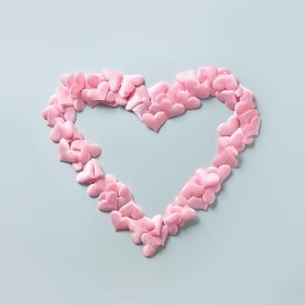 Roze harten in vorm in groot hart op blauwe achtergrond, valentijnsdag wenskaart.