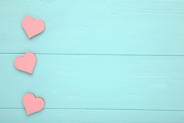 Roze harten op een blauwe houten achtergrond.