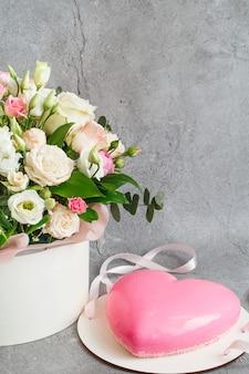 Roze hartvormige mousse cake en een groot boeket prachtige bloemen op de grijze grunge achtergrond.