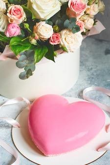 Roze hartvormige mousse cake en een groot boeket prachtige bloemen op grijs