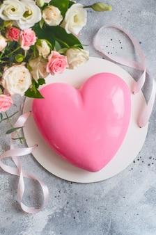 Roze hartvormige mousse cake en een groot boeket prachtige bloemen