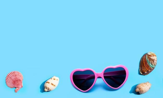 Roze hartvormige zonnebril met exotische zeeschelpen op blauw oppervlak