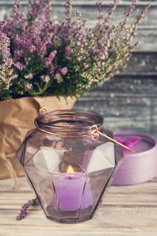 Roze heide en kaars in geometrische glazen vaas