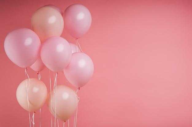 Roze helium verjaardagsballons op roze studio