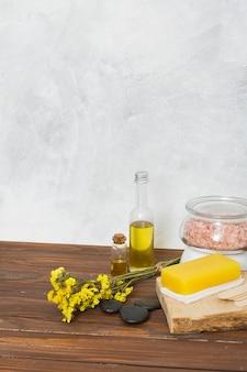 Roze himalayan zoute kruik; spons; de laatste; etherische olie en limonium bloemen op tafel