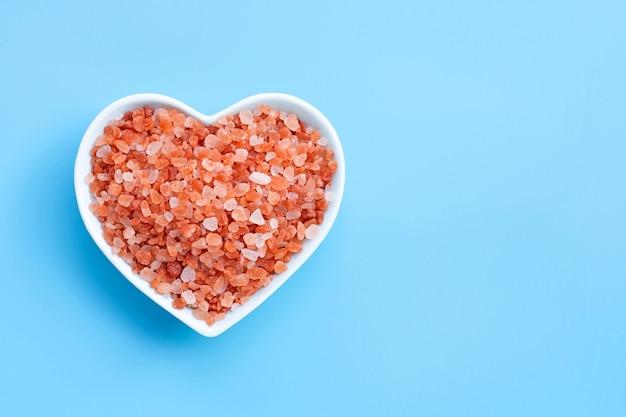 Roze himalayazout in de kom van de hartvorm op blauwe achtergrond.
