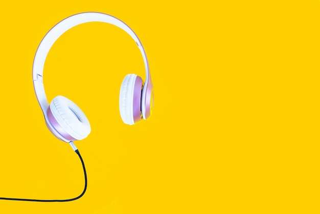 Roze hoofdtelefoon en zwarte kabel op pastelkleur gele achtergrond. muziek concept.