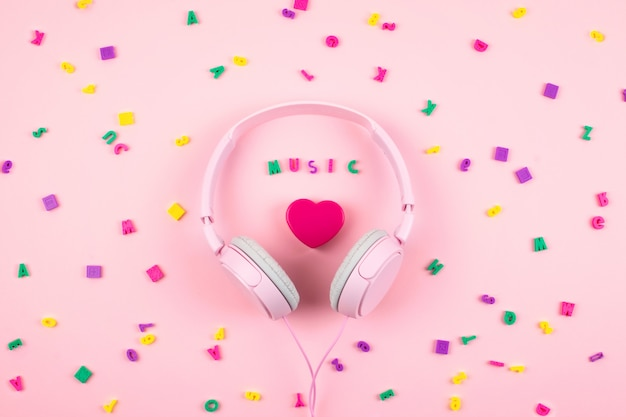 Roze hoofdtelefoons en hart met woordmuzie