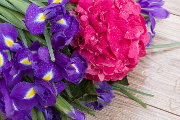 Roze hortensia en violette irisbloemen op houten bank