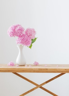Roze hortensia in witte vaas op houten plank op witte muur als achtergrond