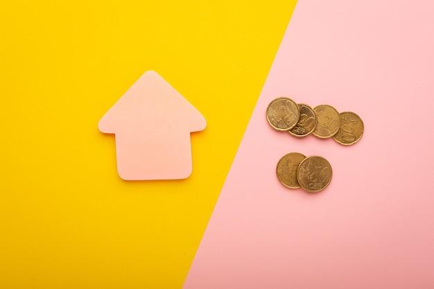 Roze huis met munten als een concept van investering in onroerend goed op gekleurd papier