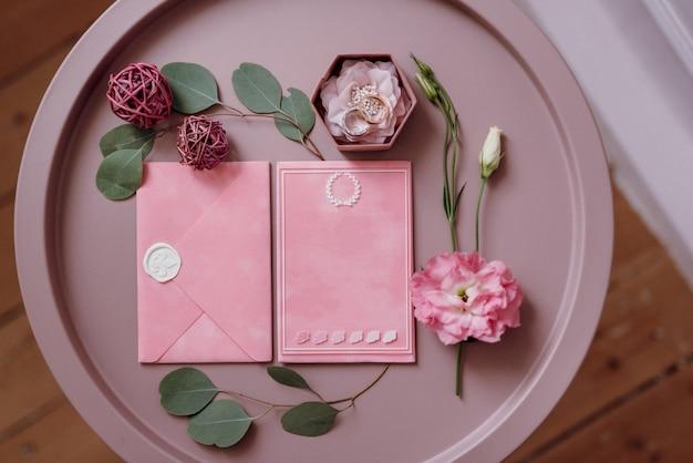 Roze huwelijksuitnodiging in een grijze envelop op een tafel met groene takjes