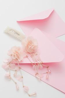 Roze huwelijksuitnodigingen zijn versierd met de haarclip en oorbellen van de bruid. concept voorbereiding voor de bruiloft.
