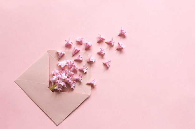 Roze hyacint in de roze envelop op de achtergrond van het papier