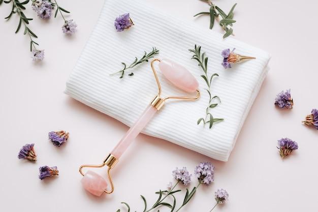 Roze hyaluronzuur serum, rozenkwarts schoonheidsroller, gua sha en paarse bloemen op roze tafelblad. anti-aging cosmetica en hulpmiddelen, kopieer ruimte, bovenaanzicht