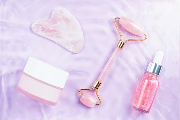 Roze hyaluronzuurserum, rozenkwartsroller, gua sha en gezichtscrème in water, bovenaanzicht. anti-aging cosmetica in roze water, bovenaanzicht. glamoureuze schoonheidsproducten achtergrond in roze en violette kleuren