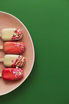 Roze ijslollycakes op een groene achtergrond