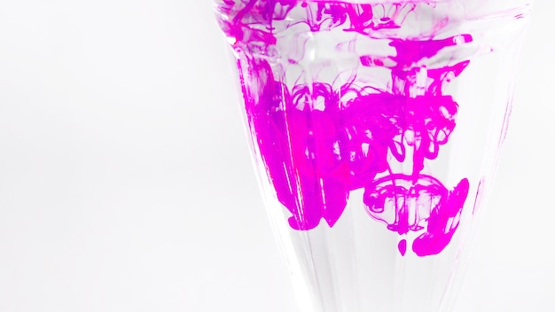 Roze inkt die zich in het transparante glas tegen witte achtergrond mengt