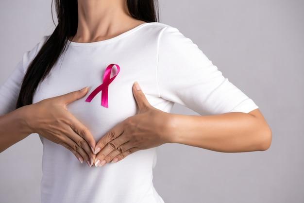 Roze insigne lint op de borst van de vrouw om de oorzaak van borstkanker te ondersteunen. gezondheidszorg concept.