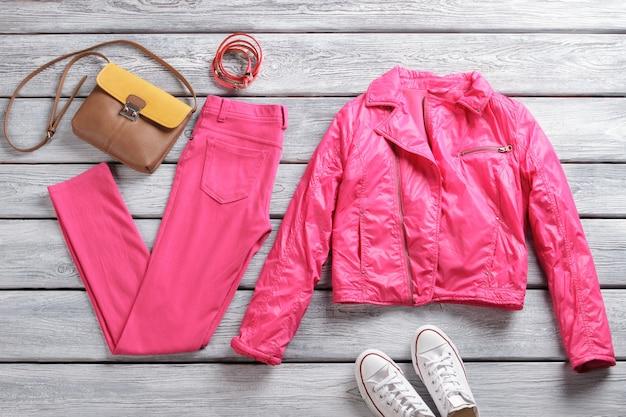 Roze jas en broek. witte canvas schoenen en broek. heldere bovenkleding en stijlvolle accessoires. casual outfitidee voor de lente.