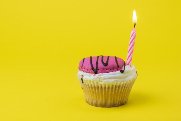 Roze kaars in bessen cupcake. het concept van de verjaardag.