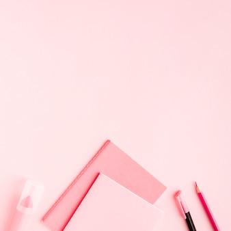 Roze kantoorbenodigdheden op gekleurd oppervlak
