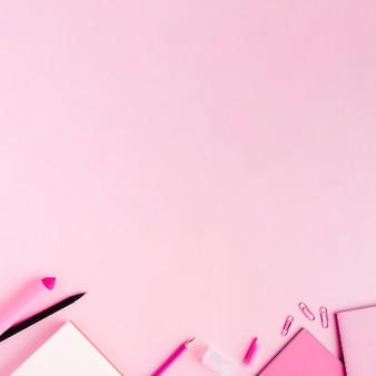 Roze kantoorbenodigdheden op gekleurde oppervlak
