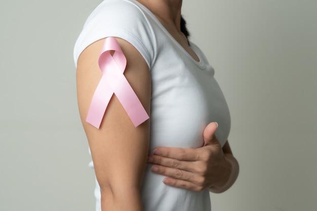 Roze kentekenlint op vrouwenarm ter ondersteuning van de oorzaak van borstkanker. borstkanker bewustzijn concept