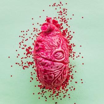 Roze keramisch menselijk hart met lovertjes op tafel