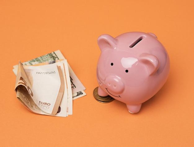 Roze keramisch spaarvarken en euro bundel, besparingen en investeringsconcept, sluit omhoog