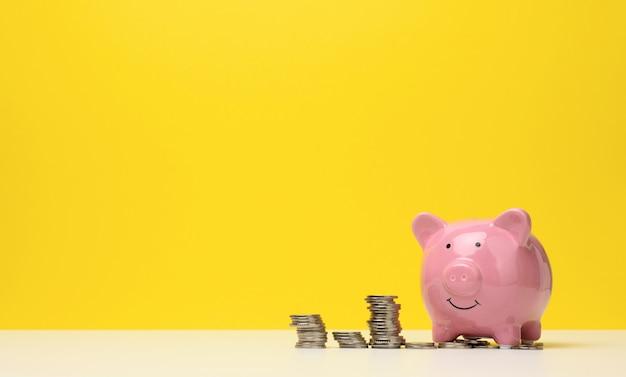 Roze keramische spaarvarken en een stapel munten op een witte tafel, gele achtergrond. besparingen concept, budgetplanning. inkomensgroei, kopieer ruimte