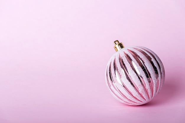 Roze kerstbal, glanzende bal op pastel achtergrond.