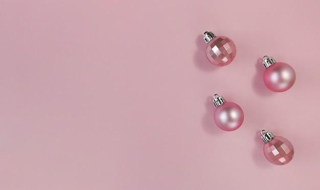 Roze kerstballen op een pastelpapier. eenvoudig plat leggen met kopie ruimte.