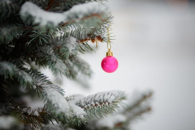 Roze kerstboomballen in de kleuren van de vlag van oekraïne. speelgoed op besneeuwde boom