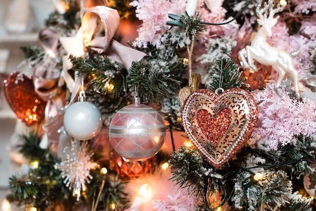 Roze kerstversiering, briefkaart. op de boom een hart, ballen en een krans.