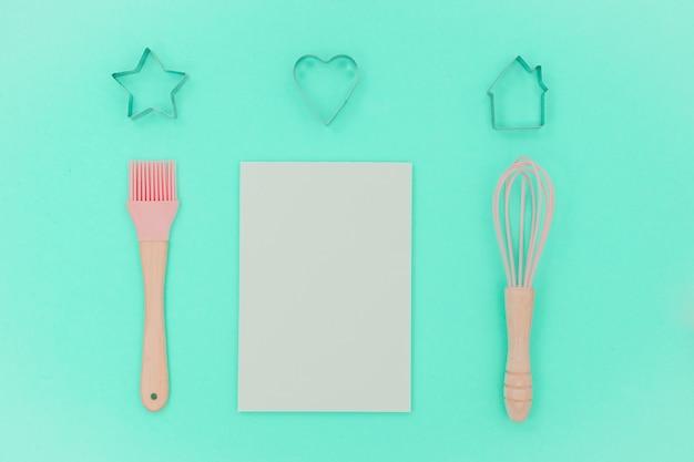 Roze keukengerei met lege notitie. groter, klop en ijzer kookvorm. bovenaanzicht
